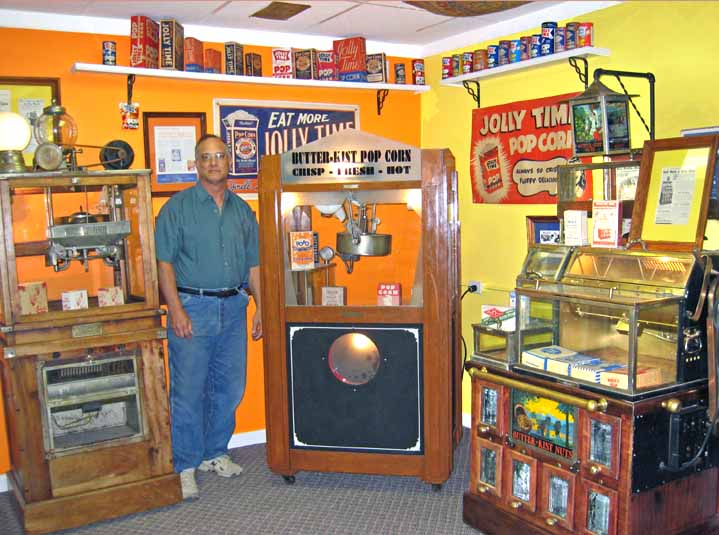Jim Fentress standing left of the rare deco-style Prosperity Butter-Kist popcorn machine from Holcomb & Hoke